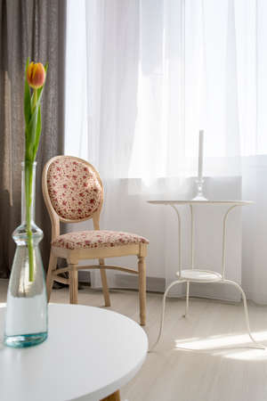 upholstered: Small table and stylish upholstered chair standing in light living room