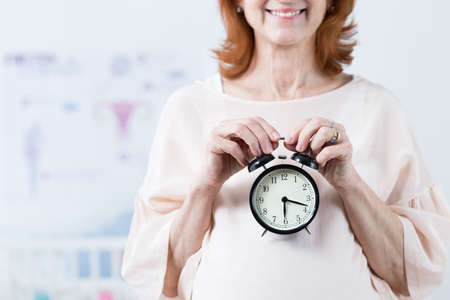 Male biological clock ticking- cheerful pregnant mature woman
