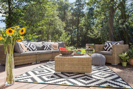 スタイリッシュな籐家具とパターン カーペットが付いているヴィラ テラス 写真素材 - 62010575