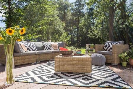 세련된 등나무 가구 및 패턴 카펫이있는 빌라 파티오 스톡 콘텐츠