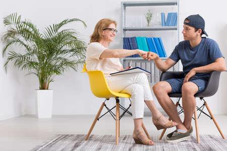전문 심리 치료사 및 그녀의 십대 환자 가벼운 방에 앉아