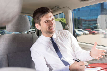 young businessman: Elegant and handsome businessman traveling on a back seat of a car Stock Photo