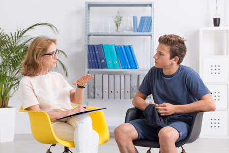 Professional psychotherapist and her teenage patient, light interior