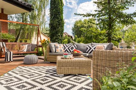 Új tervezésű villa terasz kényelmes rattan bútorok és mintás szőnyeg