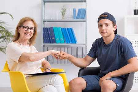 Mature woman and teenage boy giving each other a fist bump, light interior Stok Fotoğraf