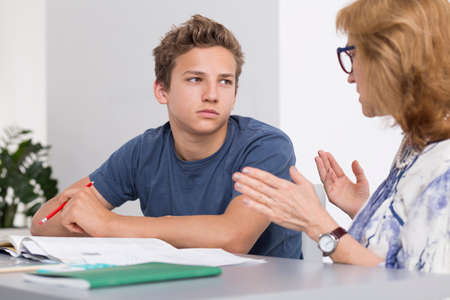 private schools: Teenage boy having private lessons with mature teacher, sitting in a light interior