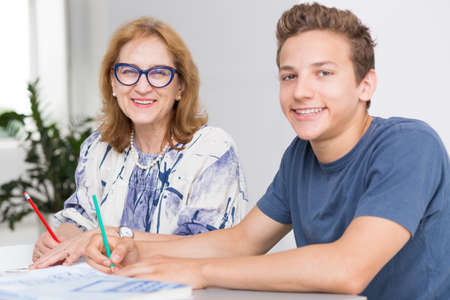 private room: Happy teenage boy and his private mature teacher sitting in a light interior Stock Photo