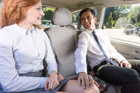 sexual: Handsome businessman holding his hand on a womans leg, sitting on a back seat of acar