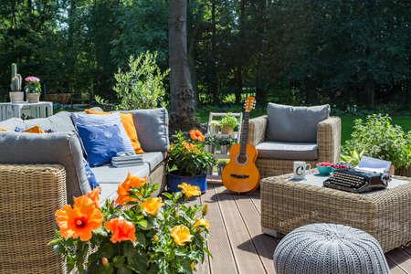 등나무 소파, 안락 의자 및 작은 테이블이있는 고급스러운 빌라 파티오