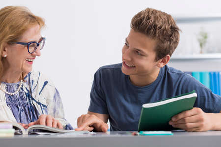 Smiling teenage student and his private teacher sitting in a light interior Stock Photo