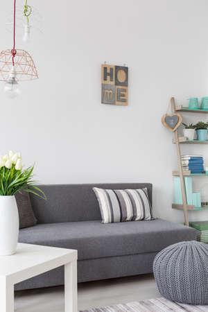 hassock: Grey comfortable sofa and hassock in scandinavian modern interior