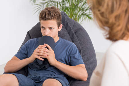 Depressed teenager talking with a mature psychologist, light interior Archivio Fotografico