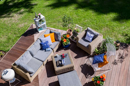 Top view of a villa patio with wooden flooring ana rattan furniture set