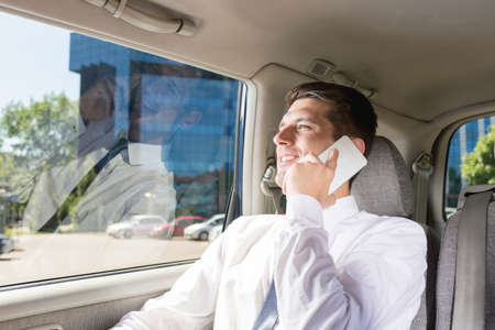 men talking: Handsome businessman talking on a cellphone on a back seat of a car