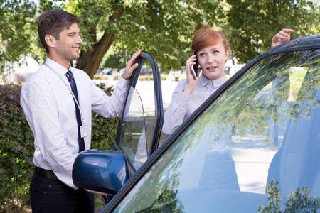 abriendo puerta: Pareja de negocios hablando por teléfono celular y la apertura de puerta de cabina del conductor y guapo Foto de archivo
