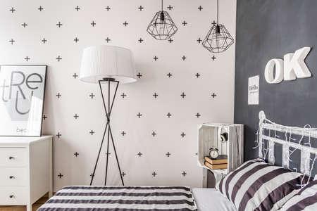 Nuevo estilo dormitorio con la pared de pizarra, ropa de cama y la lámpara de pie patrón sencillo Foto de archivo