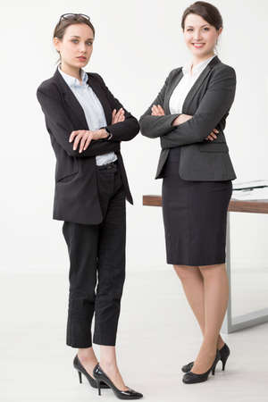 Two formally dressed women in a professional pose, standing by the desk in a very bright office Imagens