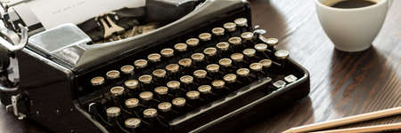 Close-up of a black vintage typewriter with round buttons, on a wooden desk
