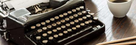 Close-up van een zwarte vintage schrijfmachine met ronde knoppen, op een houten bureau