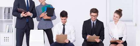 acoso laboral: Los asesores de pie detr�s de las personas j�venes, elegantes haciendo tareas durante el curso de formaci�n Foto de archivo