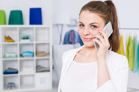 Young woman with cellphone standing at light fashion studio interior Stock Photo