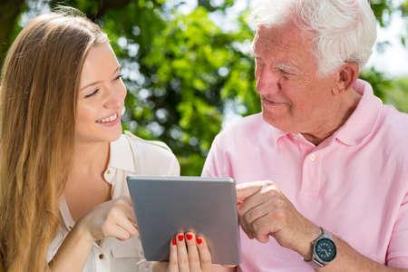 Jonge verzorger en senior man met behulp van tablet, tijd doorbrengen in het park
