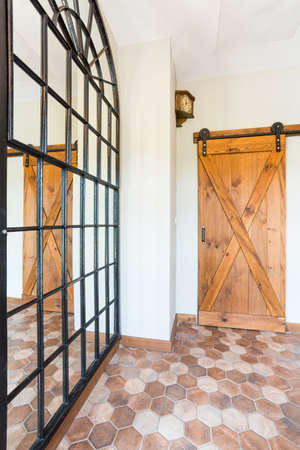 Spacious Corridor With A Big Mirror On The Wall And Cottage Style, Massive  Wooden Door