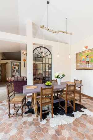dining table and chairs: Spaceful dining room area with wooden table and chairs, painting on the wall and asymetrical carpet