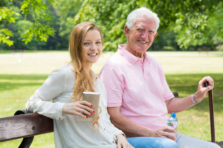 Young woman sitting on a park bench with her happy grandfather Stock Photo