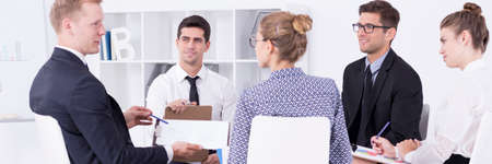 acoso laboral: Grupo de gente elegante que se sienta en el escritorio com�n y discusiones