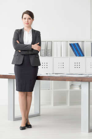Young professionally-looking woman in a grey suit standing by a desk in a bright office