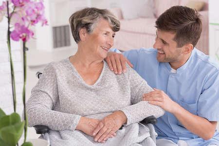 Imagen de una mujer senior sonriente y su cuidador masculino, interior de luz