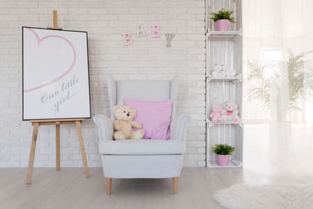 Bright and well-lighted interior with the easel, armchair with a teddy bear and cushion on and case made by wooden chests
