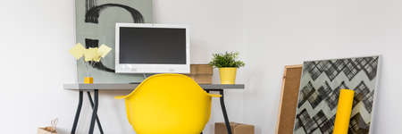 working area: Home working area with minimalistic desk and modern yellow armchair Stock Photo