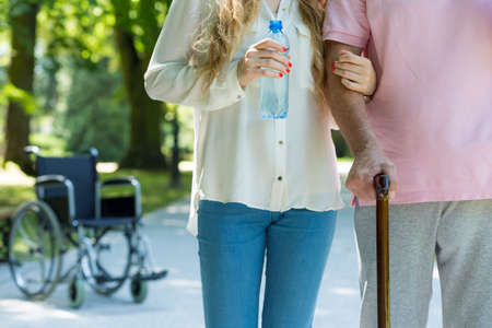 Close up of a young carer and senior with a walking stick, a wheelchair in the background Stock Photo