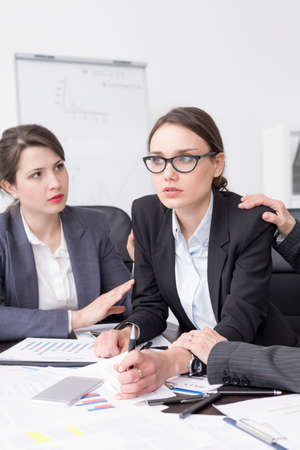 smartly: Very anxious businesswoman at an office desk, with her colleagues calming her down