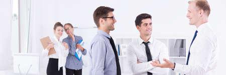 workplace harassment: Grupo de hombres en ropa elegante hablar unos con otros en la oficina Foto de archivo
