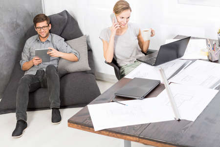bean bag: Young woman sitting at the desk in an office and talking on her mobile phone and the man with a tablet sitting on a bean bad chair behind her Stock Photo