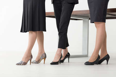 tacones negros: Disparo de piernas delgadas de tres mujeres en tacones altos y ropa formal