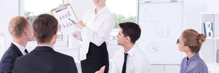 workplace harassment: Mujer joven que muestra los resultados del rendimiento corporativo a sus compañeros de trabajo Foto de archivo