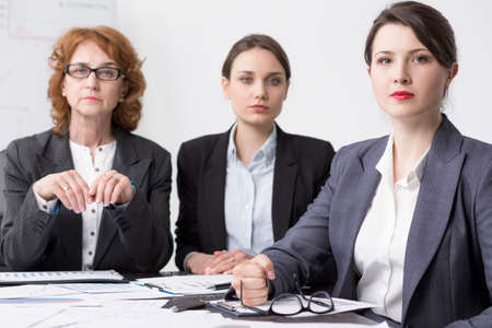 Serious businesswomen at a desk filled with documents, giving severe looks at the camera