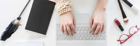 escritorio blanco con una mujer escribiendo en un ordenador portátil, rodeado de accesorios de moda Foto de archivo