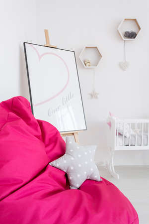 amenities: Close shot of a pink bean bag chair with star cushion and baby cradle and easel behind