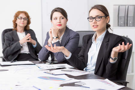 businesslike: Three female professionals sitting at a desk full of papers in a corporate office