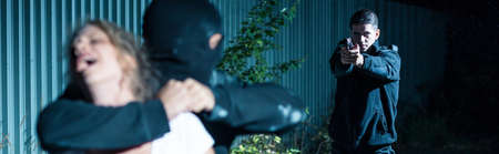 defenceless: Police officer is aiming to the kidnapper Stock Photo