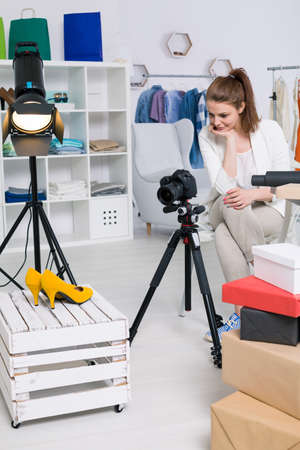 Woman taking picture of a yellow pair of shoes at light studio interior Stock Photo