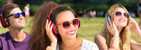 escuchando musica: Group of young people listening to the music using the earphones