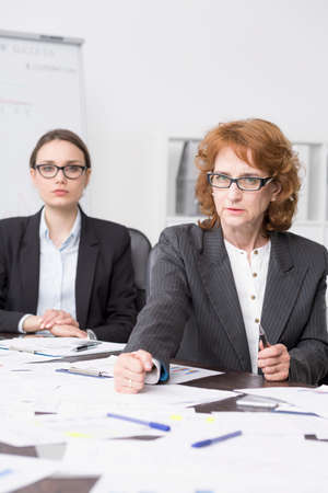 smartly: Two formally-dressed businesswomen looking angrily at the camera, one of them clenching her fists