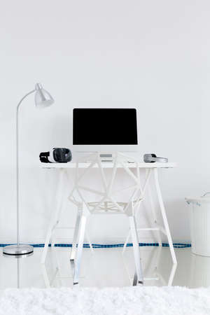 office wall: Light study room with floor lamp, white desk, crystal chair and computer Stock Photo