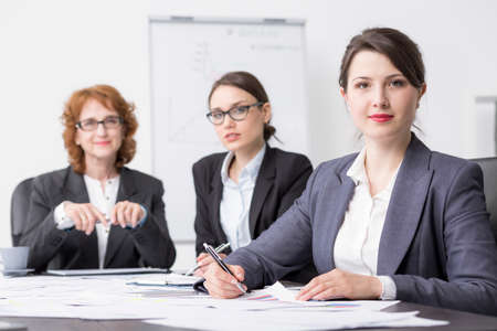 superior: Three professional women at an office desk, smiling and looking at the camera Stock Photo